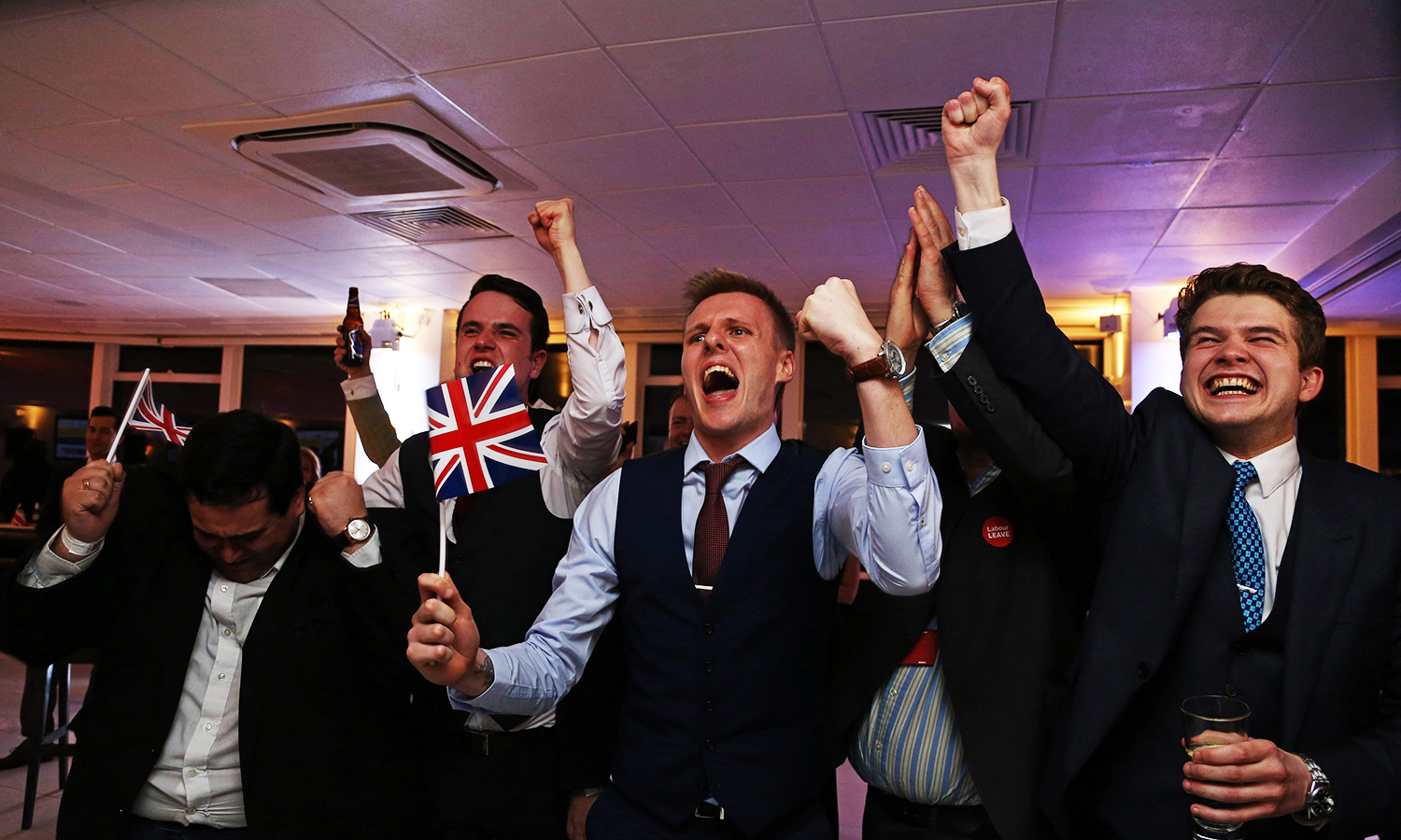Leave.EU supporters wave Union flags and cheer as the results come in at the Leave.EU referendum party at Millbank Tower in central London early in the morning of June 24, 2016. First results from Britain's knife-edge referendum showed unexpectedly strong support for leaving the European Union on Friday, sending the pound plummeting as investors feared a historic blow against the 28-nation alliance. / AFP PHOTO / GEOFF CADDICK
