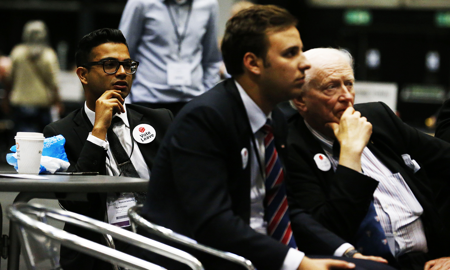 """Pro-Leave campaigners watch TV screens as results begin to come in at the Manchester Central Convention Complex where the EU referendum vote count is taking place in Manchester, north west England on June 23, 2016. First results from Britain's historic EU referendum suggest an extremely tight race, with swathes of northern England backing """"Leave"""" but parts of London and Scotland coming out strongly for """"Remain"""". / AFP PHOTO / Lindsey PARNABY"""