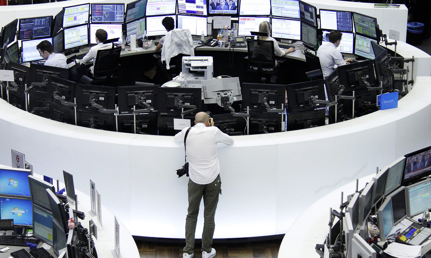 A photographer takes pictures of traders before the opening of the German stock exchange in front of the empty DAX board, at the stock exchange in Frankfurt, Germany, June 24, 2016 after Britain voted to leave the European Union in the EU BREXIT referendum. REUTERS/Staff/Remote