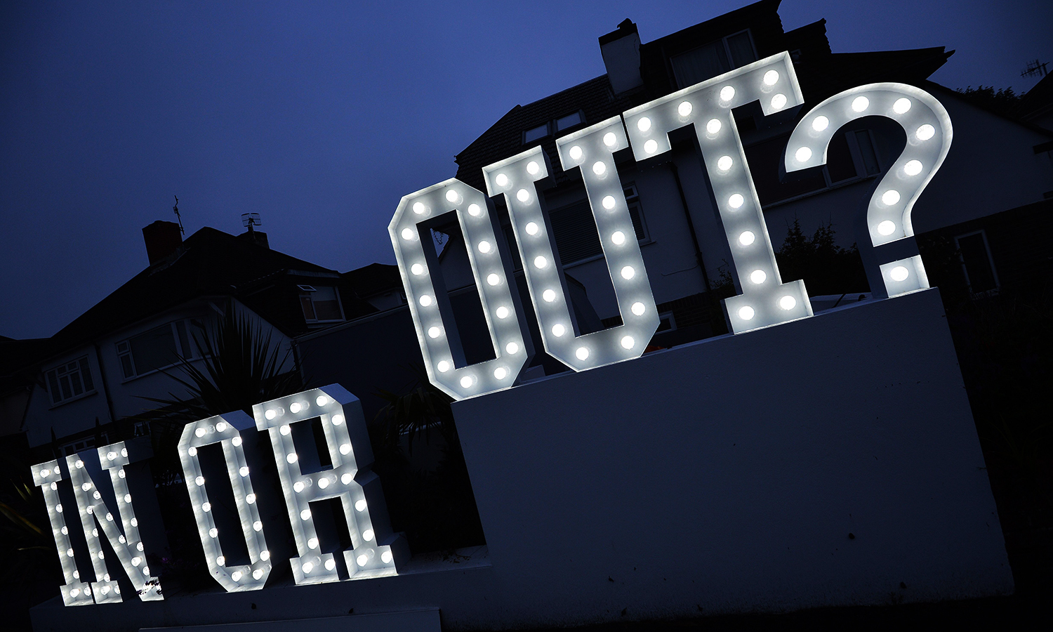 """An illuminated """"In or Out"""" sign is pictured outside a house in Hangleton near Brighton in southern England, on June 23, 2016, as Britain holds a referendum on whether to stay or leave the European Union (EU). Millions of Britons began voting Thursday in a bitterly-fought, knife-edge referendum that could tear up the island nation's EU membership and spark the greatest emergency of the bloc's 60-year history. / AFP PHOTO / GLYN KIRK"""